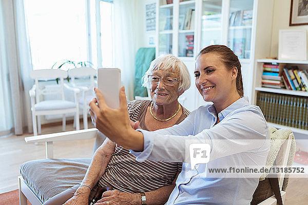 Smiling senior woman and granddaughter taking selfie using mobile phone during visit in nursing home