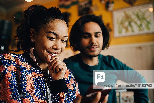 Lächelnder junger Mann und lächelnde Frau teilen sich ein Smartphone  während sie während des Brunch im Restaurant sitzen
