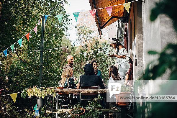 Multiethnische junge Freunde genießen während einer Party auf dem Balkon