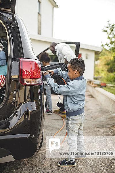 Junge in voller Länge lädt Elektroauto auf  während er auf der Einfahrt steht