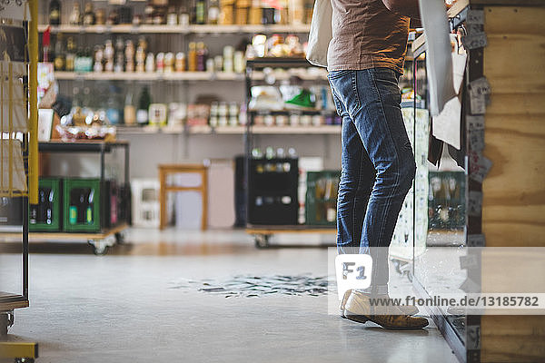 Low section of customer standing at checkout counter in deli