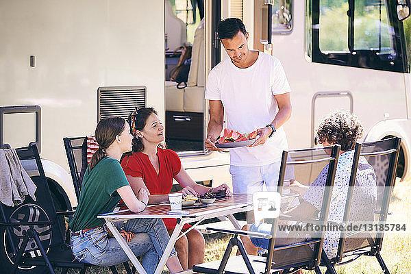 Mann serviert der Familie Wassermelonenscheiben beim Camping im Wohnwagenpark
