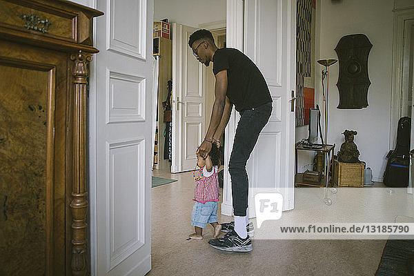 Seitenansicht des Vaters  der der Tochter zu Hause beim Gehen hilft