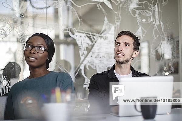Multi-ethnische Kollegen hören zu  während sie am Konferenztisch im Kreativbüro sitzen
