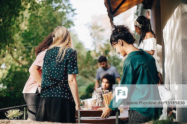 Multi-ethnische männliche und weibliche Freunde bei Tisch auf dem Balkon während der Party