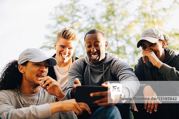 Lächelnde Freunde schauen auf Handy im Skateboard-Park