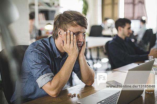 Müde Geschäftsmann schaut auf den Laptop  während er am Schreibtisch im Kreativbüro sitzt