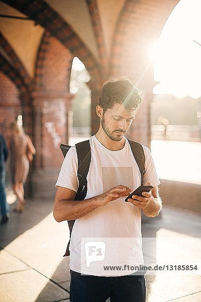 Junger Mann benutzt Smartphone  während er auf einem Fußweg in der Stadt steht