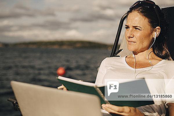 Nachdenkliche Frau mit Laptop hält Tagebuch  während sie weg gegen den See schaut