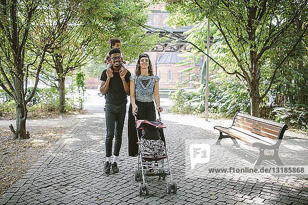 Junger Mann trägt Tochter auf den Schultern  während Frau Kinderwagen am Fussweg schiebt