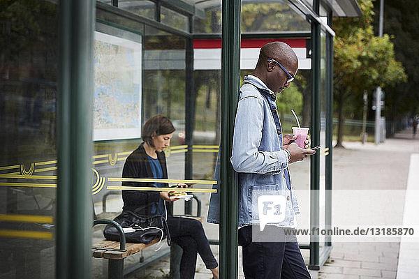 Mittlere erwachsene Pendler  die an einer Bushaltestelle in der Stadt warten