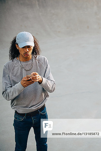 High angle view of young man using mobile phone at skateboard park