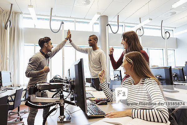 Glückliche Studenten und Studentinnen feiern Erfolge bei der Computernutzung in der Universitätsbibliothek