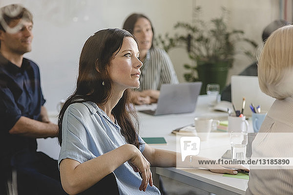 Businesswoman with colleagues listening while sitting in conference room during business meeting
