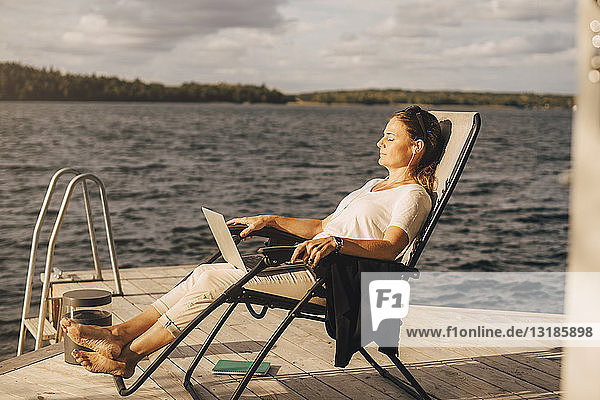 Eine Frau in voller Länge entspannt sich auf einem Liegestuhl am Steg über dem See