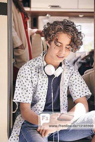 Teenager mit Kopfhörern mit Mobiltelefon im Wohnmobil