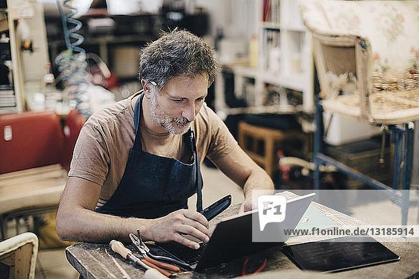 Männlicher Polsterer mit Laptop  während er an der Werkbank in der Werkstatt sitzt