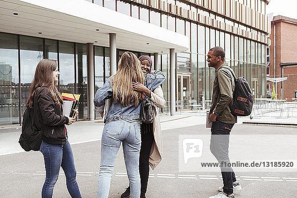 Multiethnische Freunde begrüßen im Stehen auf dem Campus der High School