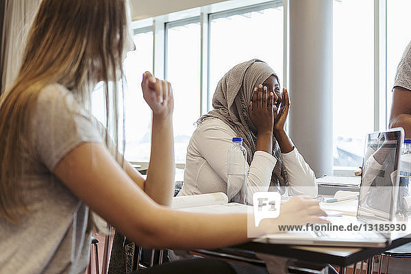 Lächelnde Frau sitzt mit Freundin am Schreibtisch im Klassenzimmer der Universität