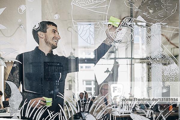 Lächelnder kreativer Geschäftsmann klebt Klebezettel auf gemustertes Glas im Büro