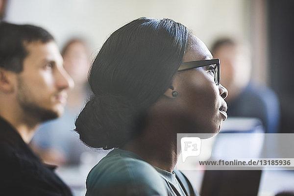 Kreative Geschäftsfrau hört während der Sitzung im Sitzungssaal zu