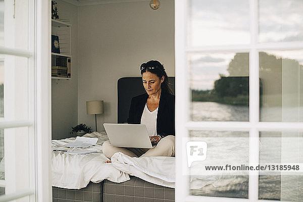 Frau mit Laptop auf dem Bett sitzend durch Türöffnung in Ferienvilla gesehen