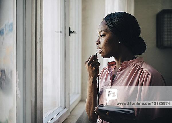 Kreative Geschäftsfrau  die durch Kopfhörer spricht  während sie im Büro am Fenster steht
