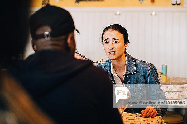 Junge Frau isst  während sie sich mit einem Freund unterhält  der während des Brunch im Restaurant sitzt
