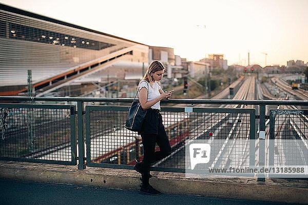 Junge Frau benutzt Mobiltelefon  während sie sich bei Sonnenuntergang an das Geländer einer Brücke in der Stadt lehnt