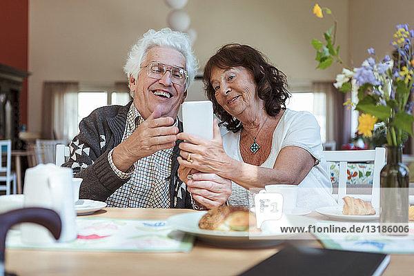 Älteres Paar  das sich während des Frühstücks im Pflegeheim mit dem Handy selbstständig macht