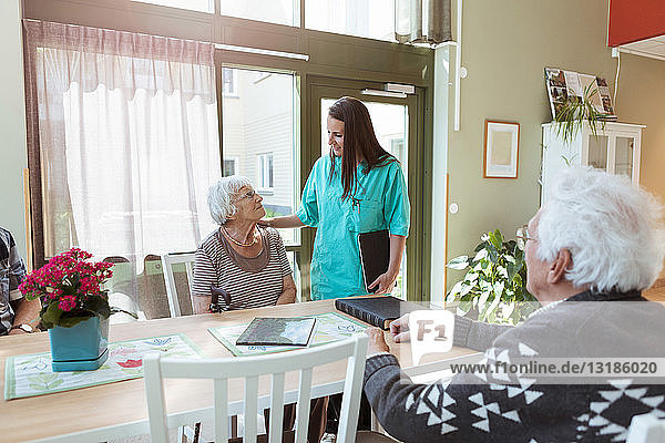 Young nurse talking with senior woman sitting at table in nursing home