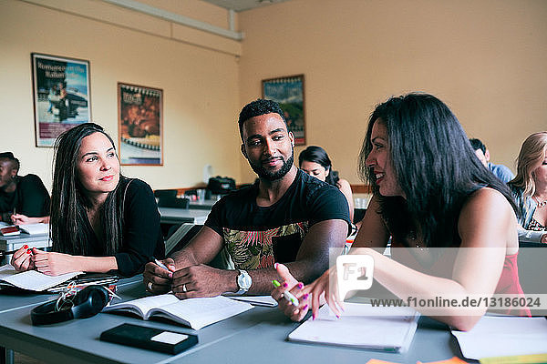 Multi-ethnic friends talking while sitting at desk in classroom