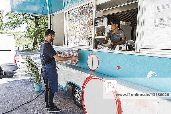 Junge männliche Besitzer kleben Poster in voller Länge auf Lebensmittelwagen in der Stadt