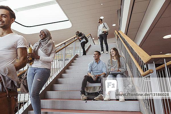 Lächelnde Studenten sitzen auf Stufen  während sie Freunde an der Universität anschauen