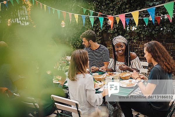 Junge männliche und weibliche Freunde genießen das Essen bei Tisch während der Dinnerparty im Hinterhof