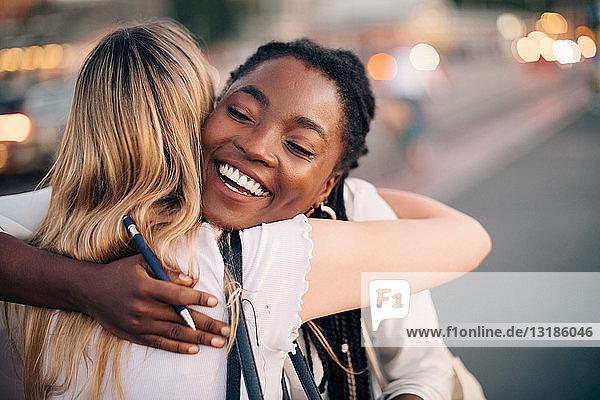 Multi-ethnische Freundinnen  die sich auf der Straße in der Stadt umarmen