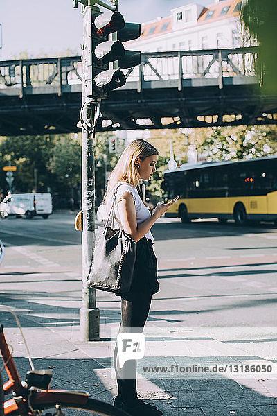 Seitenansicht einer jungen Frau  die ein Mobiltelefon benutzt  während sie auf dem Bürgersteig steht