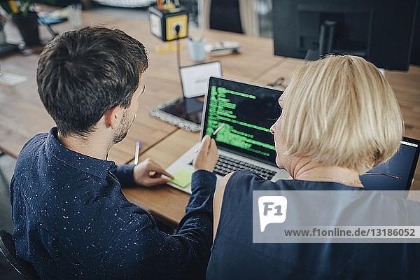 Männliche und weibliche Computerprogrammierer diskutieren über Laptop am Schreibtisch im Kreativbüro