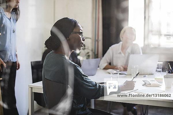 Geschäftsfrau mit Kollegen am Konferenztisch im Sitzungssaal
