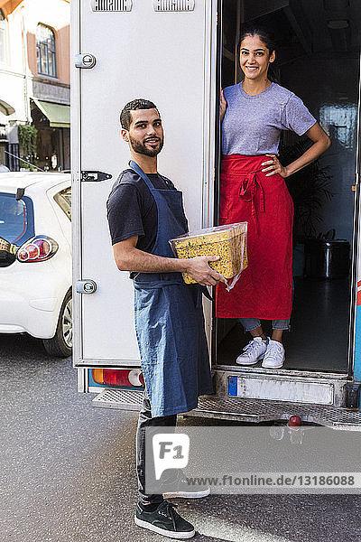 Ganzflächiges Porträt selbstbewusster junger multiethnischer Kollegen  die am Speisewagen in der Stadt stehen
