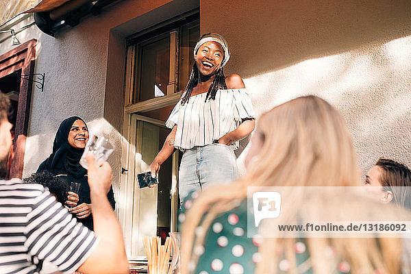 Multi-ethnische junge Freunde feiern während der Party auf dem Balkon