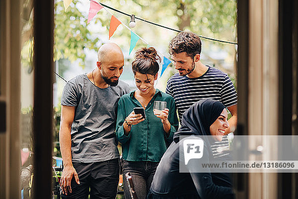 Smiling young woman showing mobile phone to male friends while standing in balcony during party