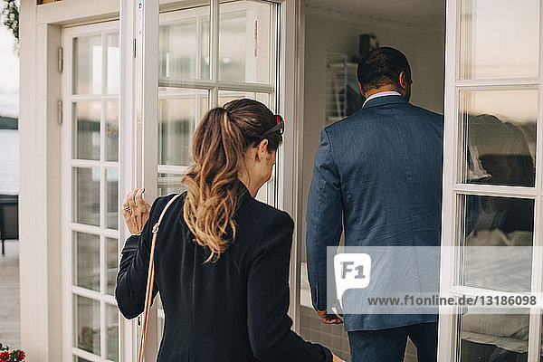 Rear view of mature couple entering holiday villa