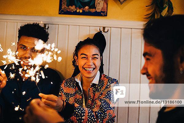 Fröhliche junge multi-ethnische Freunde sitzen mit brennenden Wunderkerzen im Restaurant