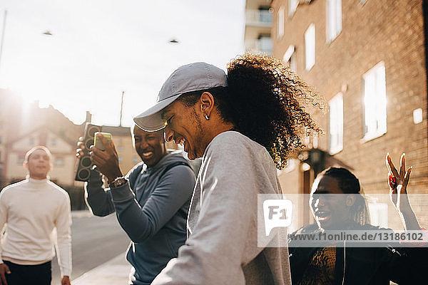 Mann hält Redner  während Freunde an einem sonnigen Tag in der Stadt tanzen