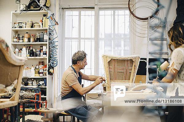 Entrepreneurs making furniture in upholstery workshop