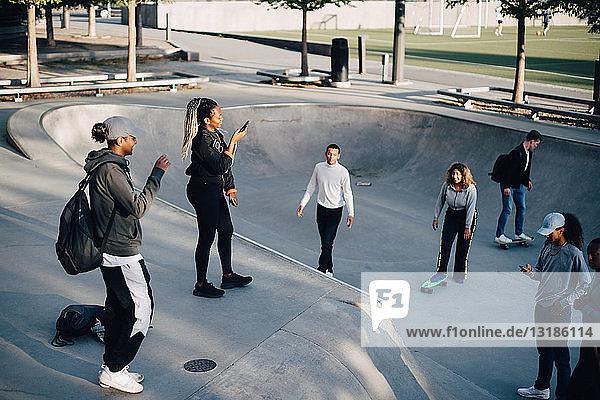 Schrägansicht von Freunden beim Mobiltelefonieren und Skateboarden im Park