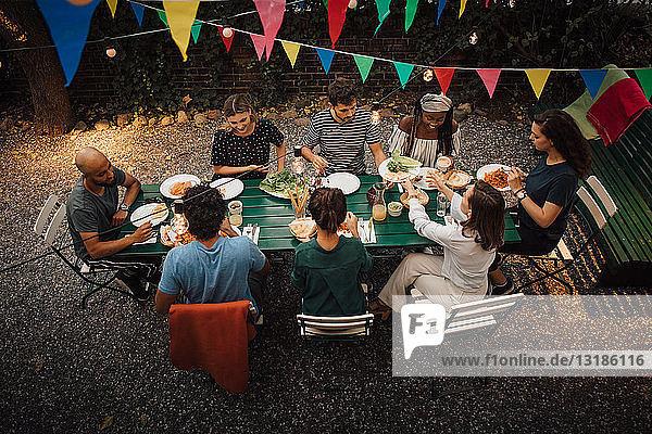 Schrägaufnahme von multi-ethnischen Freunden  die während einer Dinnerparty im Hinterhof zu Tisch sitzen