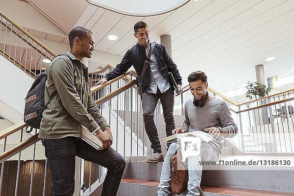 Lächelnde männliche Freunde diskutieren über Buch über Schritte in der Universität