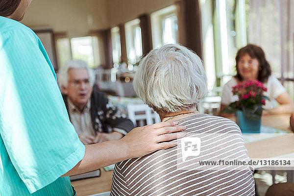 Krankenschwester  die sich um ältere Menschen in einem Pflegeheim kümmert